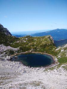 Laghetto Luznici e sullo sfondo il Matajur e la Pianura friulana